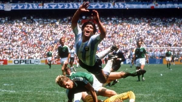 Diego Armando Maradona (Argentinien) hebt theatralisch ab, dahinter Karl-Heinz Förster und Torwart Harald Schumacher (b
