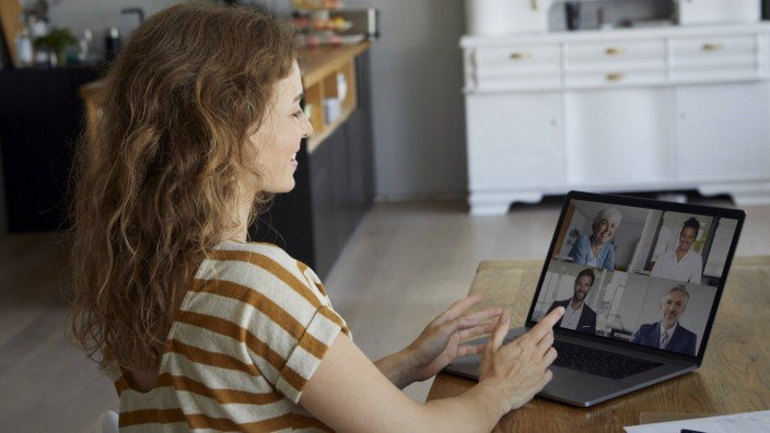 Woman talking on video conference through laptop while sitting at home model released Symbolfoto property released RBF08