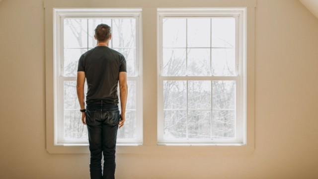 man stands in front of interior window in empty lonely minimalist room Poland, ME, United States PUBLICATIONxINxGERxSUI