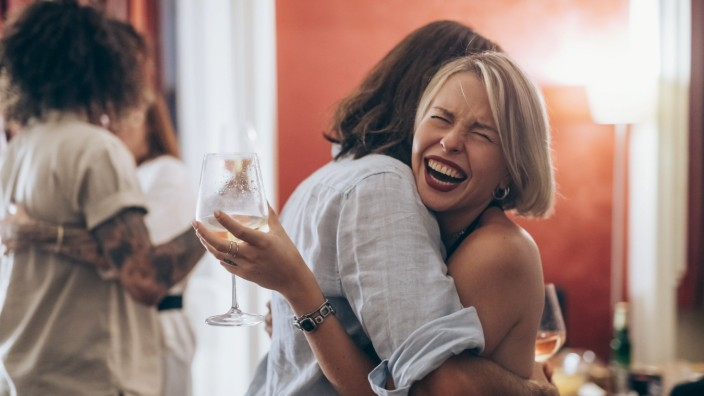 Happy young woman embracing male friend during party at home model released Symbolfoto property released MEUF02018