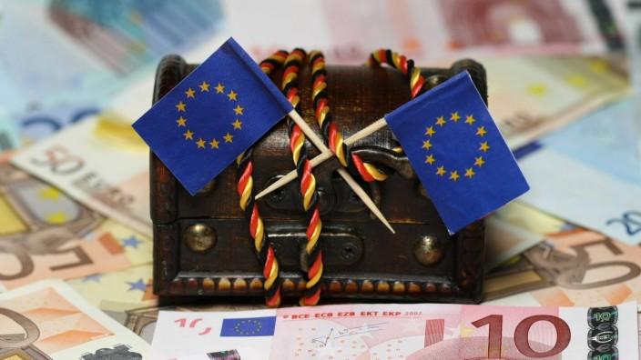 mit Kordel in den Farben der Bundesrepublik Deutschland umwickelte, verschlossene Schatztruhe mit Fahnen der EU Europäi