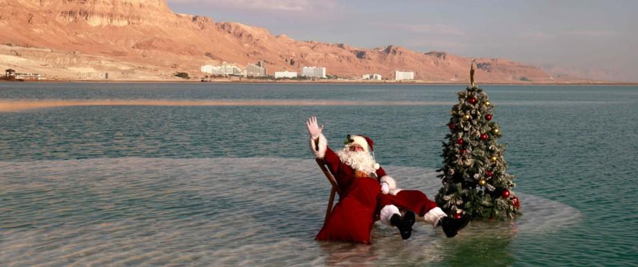 Ein Weihnachtsmann sitzt im Toten Meer.