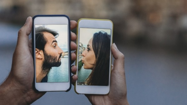 Conceptual shot of a young adult couple kissing via mobile phone; Gettyimages