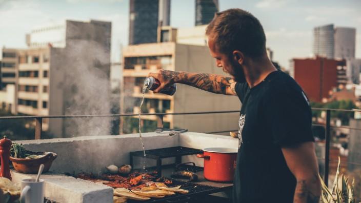 Thomas Kosikowski bereitet auf einer Dachterrasse im Mexiko-Stadt ein BBQ vor.