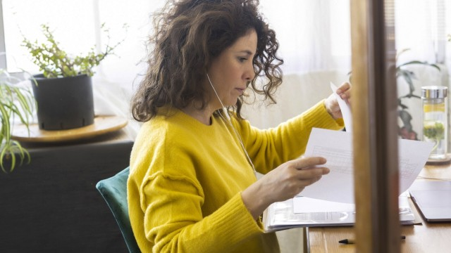 Woman working at desk in home office reviewing documents model released Symbolfoto property released ERRF03760