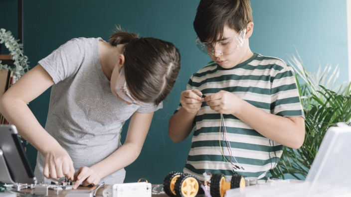Siblings making robotic toy on table at home model released Symbolfoto property released ALBF01535