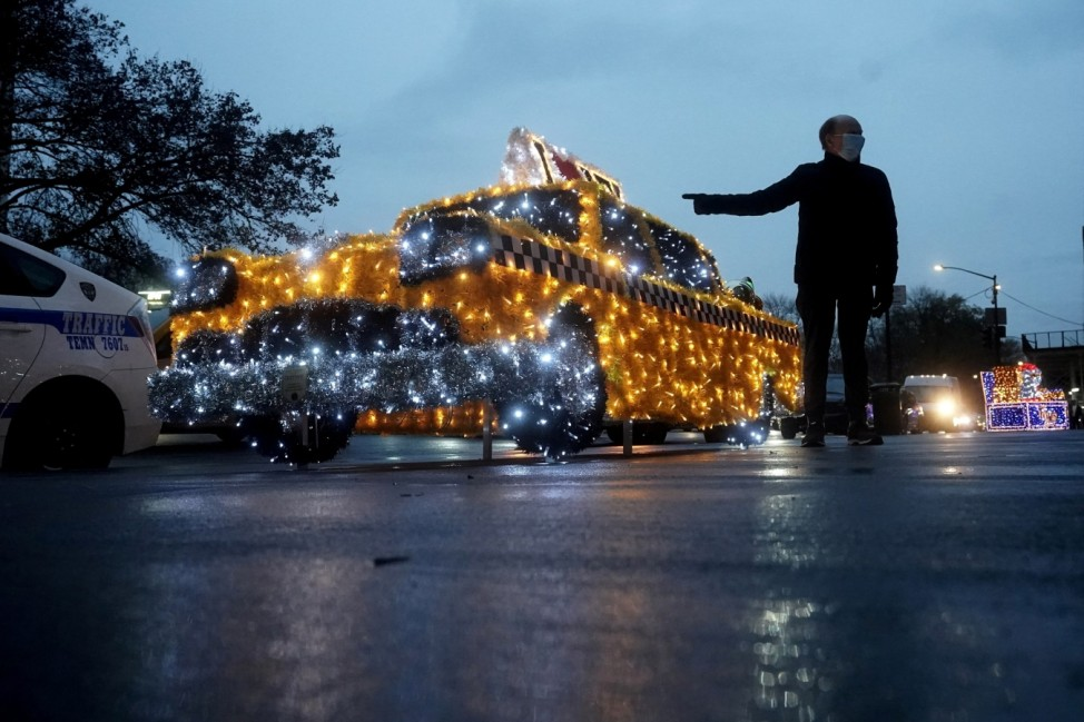 A man points at a taxi cab made of Christmas lights called 'Christmas Cab' that sits on the sidewalk of Fifth Avenue during a holiday season installation during the coronavirus (COVID-19) pandemic in the Manhattan borough of New York City, New York, U.S.