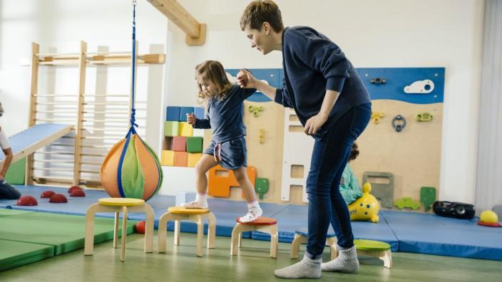 Pre school teacher helping little girl walking on steps model released Symbolfoto property released