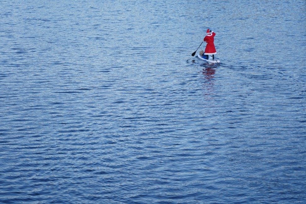 A Man Dressed As Saint Nicholas Paddle Boards On The Spree River
