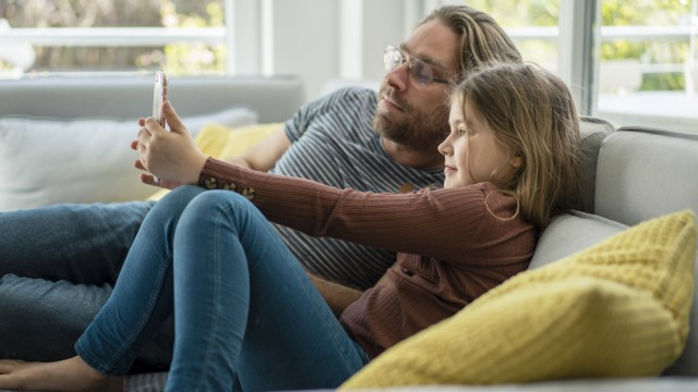 daughter taking selfie through phone with father on sofa model released Symbolfoto property released JOSEF01565