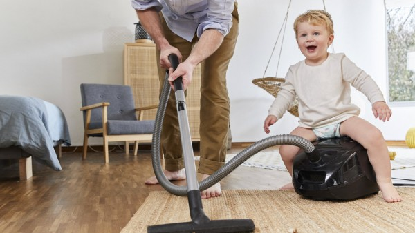 Low section of man cleaning carpet while cute baby boy sitting on vacuum cleaner in living room at home model released S
