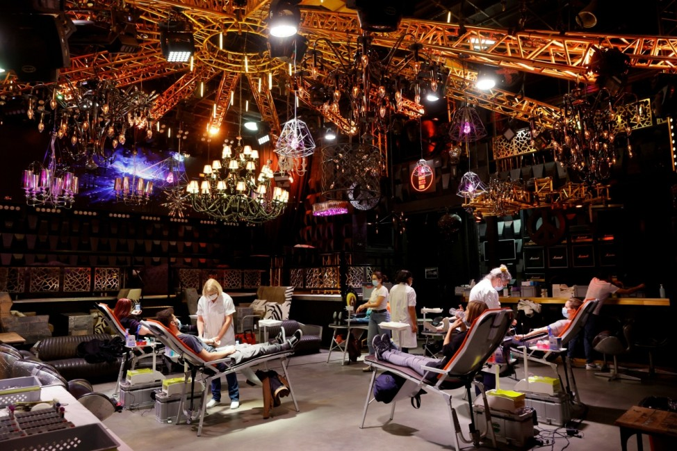 People give blood on the stage of the closed MAD (Moulin a Danse) night club in Lausanne