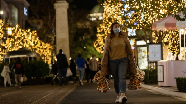 A shopper wearing a face protective mask walks by Christmas decorations at The Grove shopping center during a partial lockdown amid the outbreak of the coronavirus disease (COVID-19), in Los Angeles