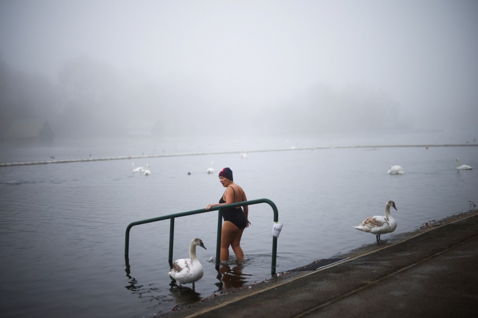 A swimmer enters the Serpentine Lake in Hyde Park during cold and foggy weather, in London