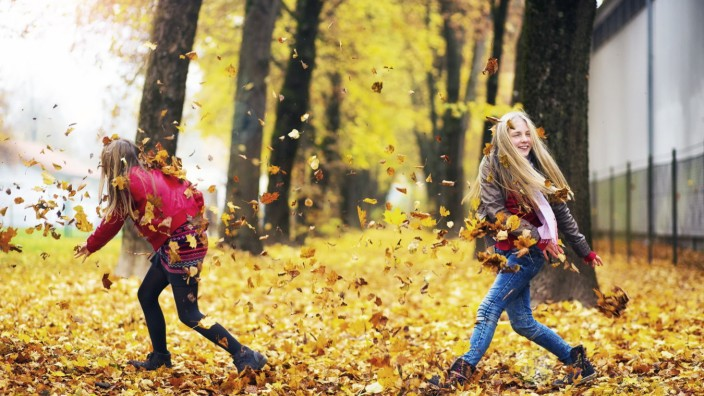 Two girls playing with autumn leaves model released Symbolfoto PUBLICATIONxINxGERxSUIxAUTxHUNxONLY M