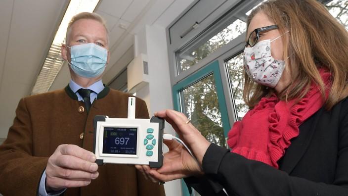 Corona: Noch brummt es: Bürgermeister Jan Neusiedl und Schulleiterin Claudia Angermaier mit dem CO2-Messgerät. Oben an der Wand der Luftreiniger.