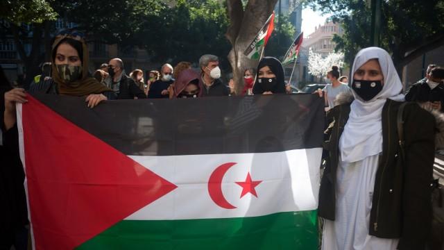 November 28, 2020, Malaga, Spain: A group of saharan demonstrators wearing face masks hold a large flag during the demo