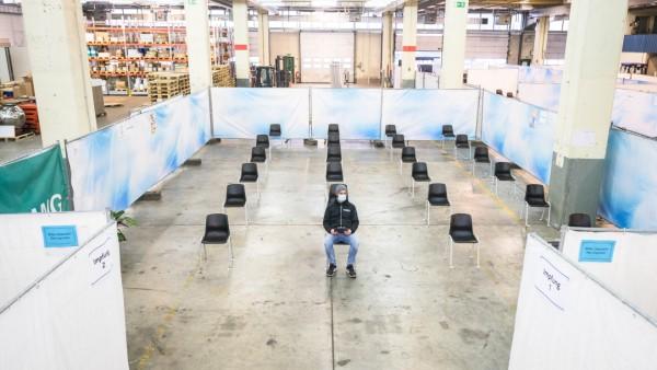 Ein Proband sitzt inmitten leerer Stühle in einem Probe-Impfzentrum in Mainz