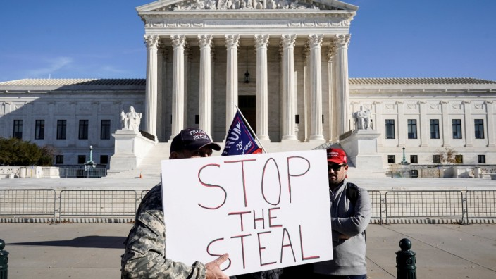 FILE PHOTO: Supporters of U.S. President Donald Trump stand at the Supreme Court in Washington