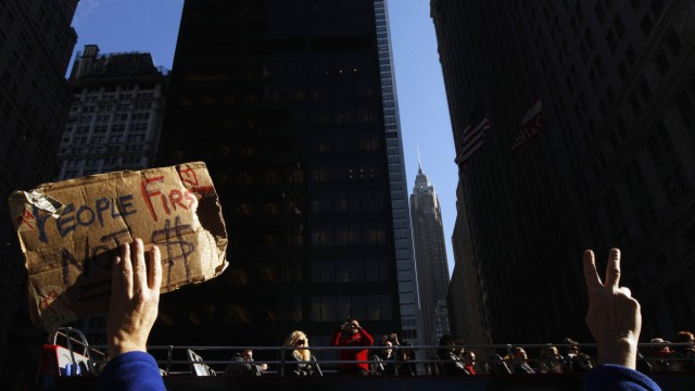 A tourist on a bus takes a photograph of a demonstrator from the Occupy Wall Street movement in Zuccotti Park in New York