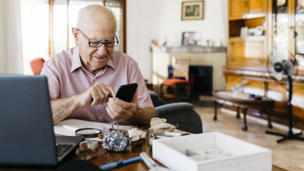 Elderly man using smart phone while doing research on mineral and fossil at home model released Symbolfoto property rele