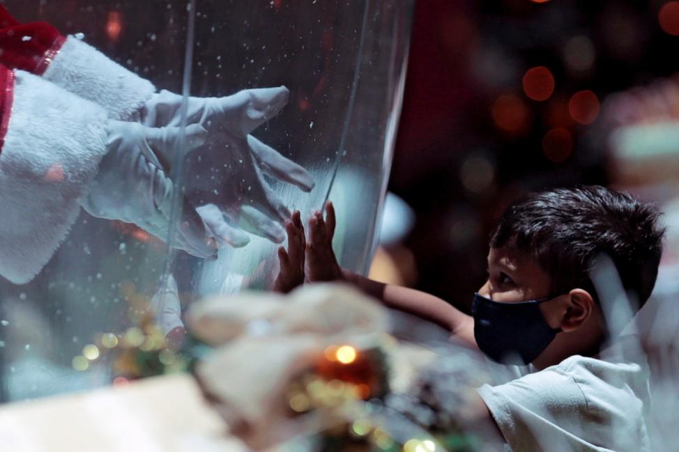 Santa Claus in bubble greets child in Brasilia