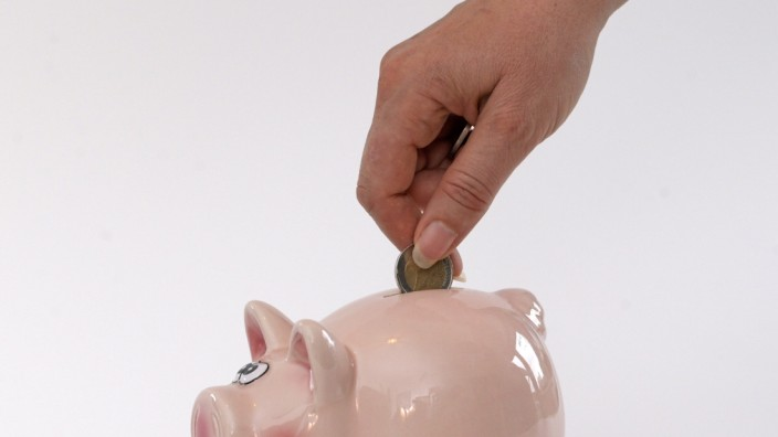 15.05.2020, Sparschwein Symbolbild, Frau steckt Zwei Euro in ein Sparschwein. 15.05.2020 Sparschwein Symbolbild 15.05.20