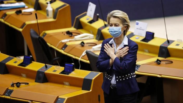 EU-Kommissionspräsidentin ursula Von der Leyen steht im Plenarsaal des Europaparlaments und kreuzt die Hände vor der Brust. Sie trägt eine EInwegmaske.