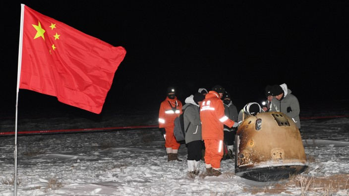 Researchers work around Chang'e-5 lunar return capsule carrying moon samples next to a Chinese national flag, after it landed in northern China's Inner Mongolia Autonomous Region