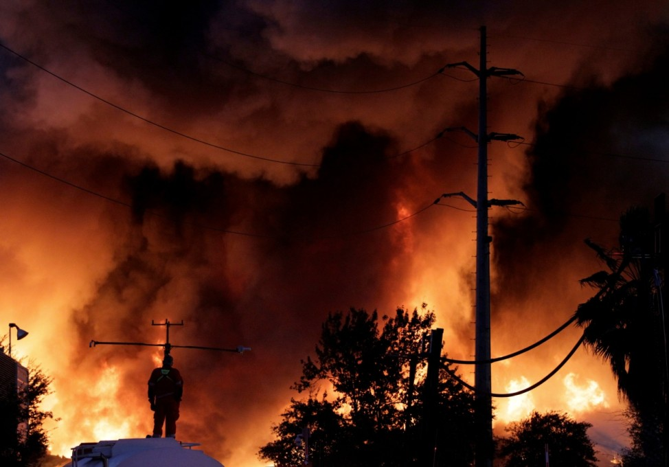 A firefighter stands on a water tank during fire in a scrap metal recycling plant of Deacero company in Guadalupe, on the outskirts of Monterrey