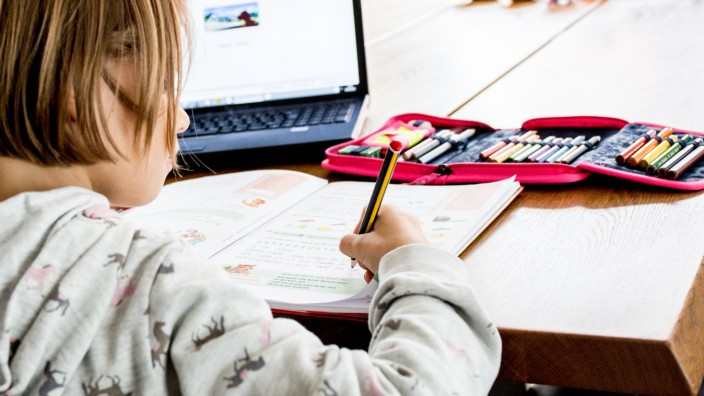 Bamberg, Deutschland 13. Dezember 2020: Ein Schulkind sitzt an einem Tisch in einer Wohnung und arbeitet mit einem Lapt