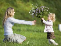 Daughter giving mother bunch of flowers side view model released PUBLICATIONxINxGERxSUIxAUTxHUNxONL