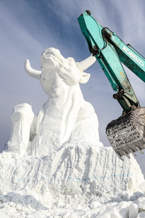 SHENYANG, CHINA - DECEMBER 26: A worker operates an excavator to build a 15-meter-tall bull snow sculpture at Qipan Mou