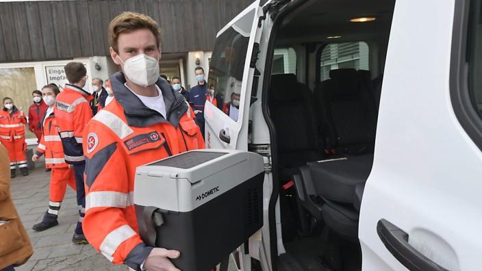 Start der Impfungen: Ausrücken zum Impfen: Ein Mitarbeiter der Johanniter lädt in Oberhaching eine Kühlbox mit Impfdosen für Altenheimbewohner ins Auto ein.
