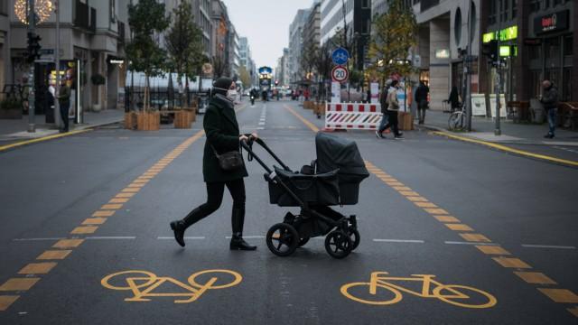 Eine Passantin mit Kinderwagen ueberquert den Radweg in der Friedrichstrasse in Berlin Mitte. Foto: bildgehege Radweg F