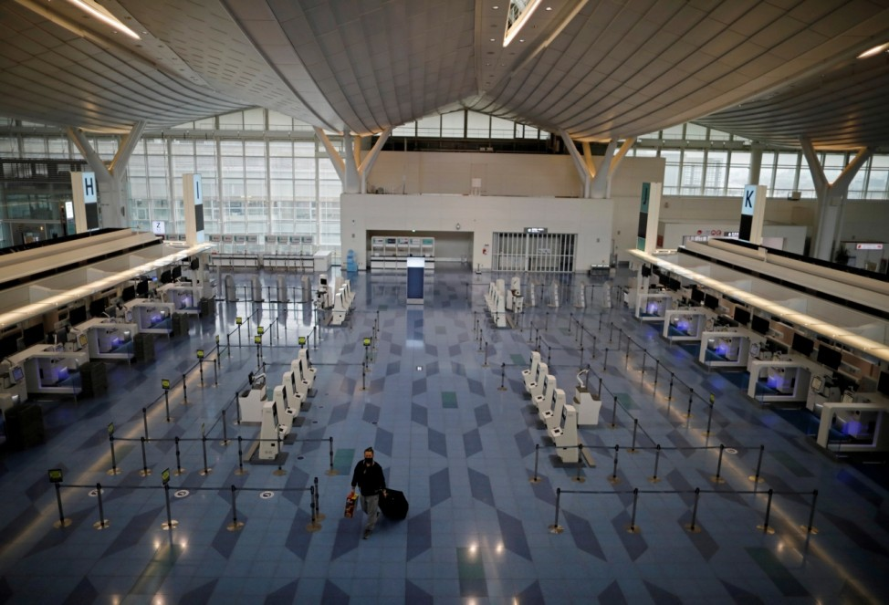 A passenger is seen at the check-in area of the international flight terminal at Haneda airport in Tokyo