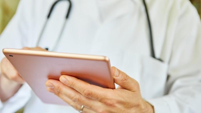 Arzt in Klinik schaut nutzt App auf Tablet Computer