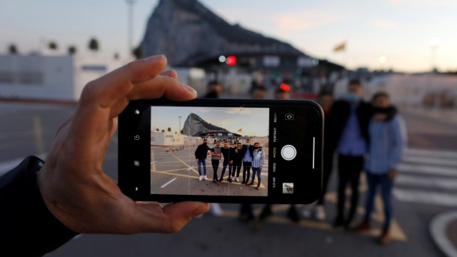 Gibraltarian citizens are seen on the screen of a mobile phone as they pose for a photo as they cross the country's border from Spanish side in La Linea de Concepcion