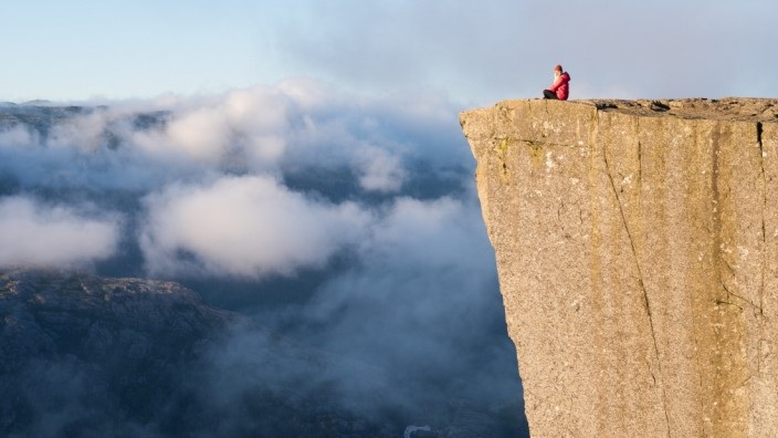 Preikestolen - amazing rock in Norway. Girl sitting on a cliff above the clouds. Pulpit Rock, the most famous tourist attraction in Ryfylke, towers over the Lysefjord (Kotenko)