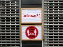 (FOTOMONTAGE) Schild mit Aufschrift Lockdown 2.0 hängt am Eingang eines mit Rolltor verschlossenen Geschäfts in der Inn