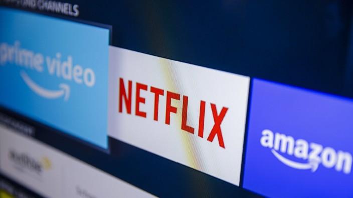 Symbolfoto: Die Logos der Streaming Dienste Amazon Prime Video, Netflix, und amazon music sind auf einem Fernseher zu s