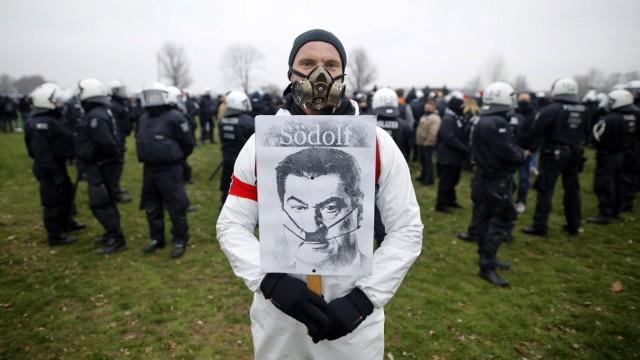 Ein Demonstrant posiert mit einem im Stile Adolf Hitler verfremdeten Konterfei von Markus Söder, betitelt als Södolf ,