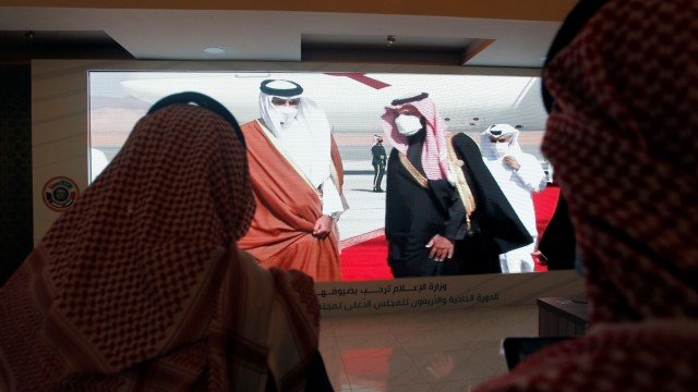 Journalists watch a screen showing the Saudi Arabia's Crown Prince Mohammed bin Salman welcoming Qatar's Emir Sheikh Tamim bin Hamad al-Thani upon his arrival to attend the Gulf Cooperation Council's (GCC) 41st Summit, at the media centre in Al-Ula