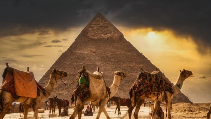 Kamelreiter und Touristen vor der weltberühmten Cheops Pyramide in Gizeh, Ägypten *** Camel riders and tourists in front
