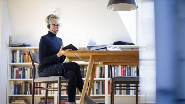 Symbolfoto zum Thema Homeoffice. Eine Frau sitzt zu Hause am Schreibtisch. Sie traegt ein Headset und nimmt an einer Vid