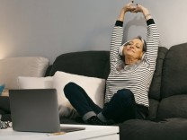 Carefree woman with hand raised listening music while sitting on sofa at home model released Symbolfoto property release