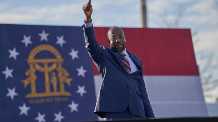 Rev. Raphael Warnock addresses crowd at drive-in rally on the eve of Georgia s Senate runoff election at Center Parc Cr