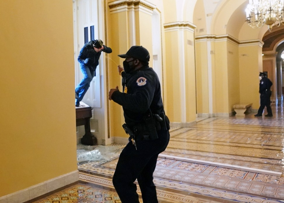 A U.S. Capitol police officer shoots pepper spray at a protestor attempting to enter the Capitol building during a join
