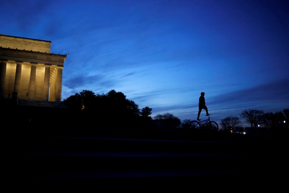 A boy stands on a bike as he rides at the Lincoln Memorial in Washington, U.S.