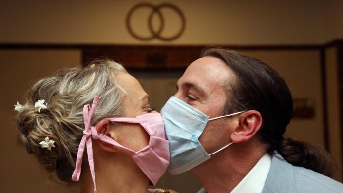 14.05.2020, Berlin, GER - Brautpaar kuesst sich in Zeiten der Coronapandemie mit Mund-Nasen-Schutz. (MR=yes, Berlin, Bez